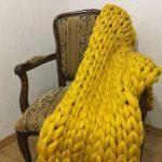 Плед крупной вязки из 100% шерсти желтого цвета очень выгодно выглядит в интерьере