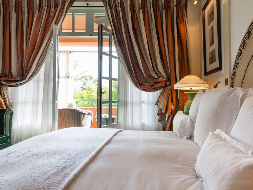 Белая кровать в спальне с полосатыми шторами