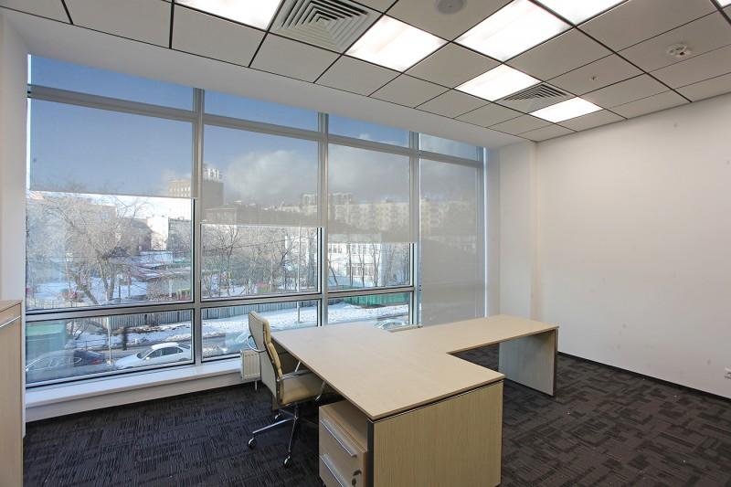 Лекие рулонные шторы на большом окне в офисе
