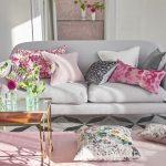 Разноцветные диванные подушки освежают интерьер серой комнаты