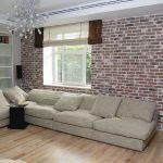 Кирпичная стена в комнате с диваном