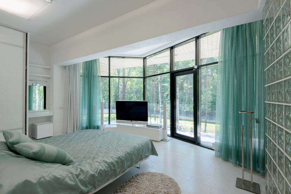 Интерьер большой спальни с бирюзовыми шторами