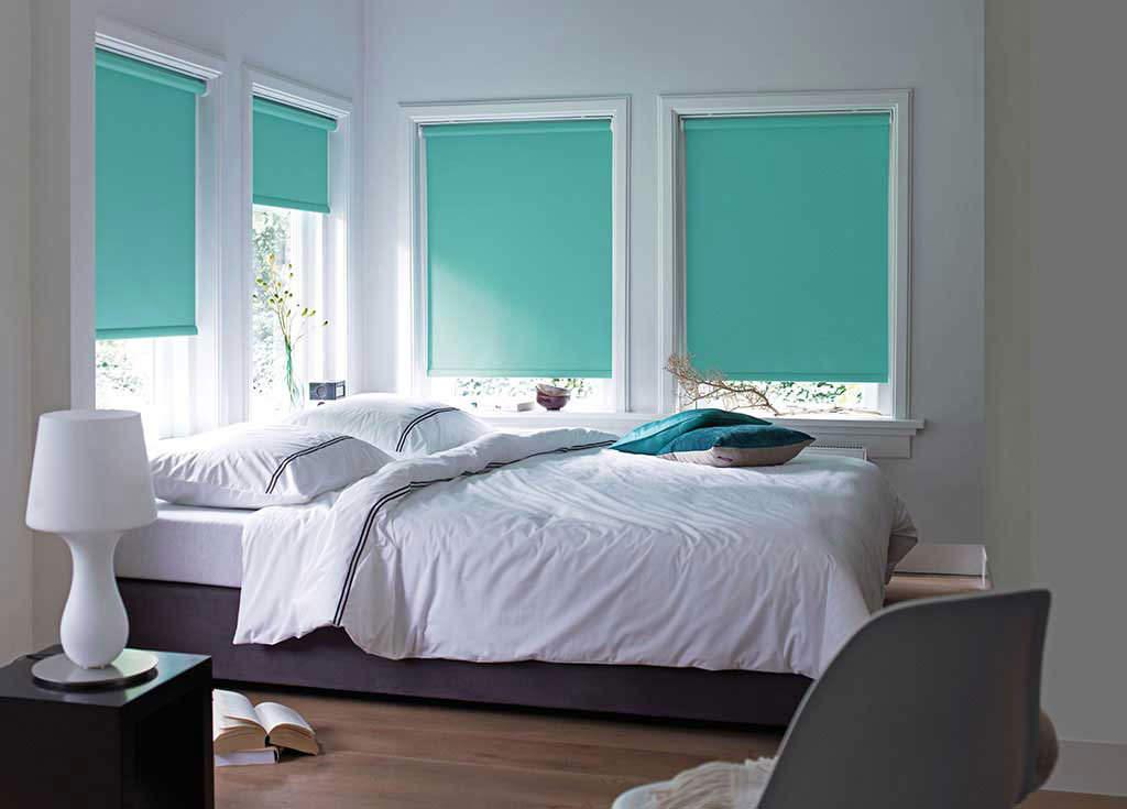 Рулонные шторы бирюзового цвета на окнах спальни