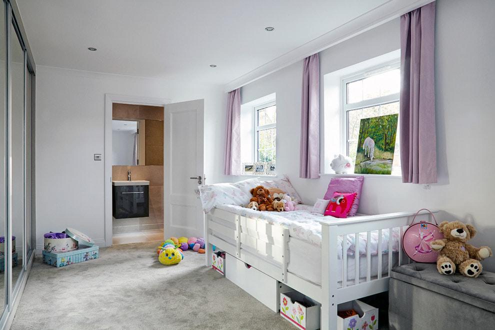 Белая детская кроватка в комнате с короткими занавесками