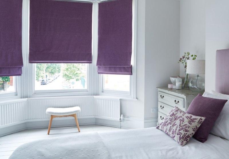 Белая спальня с римскими шторами фиолетового оттенка
