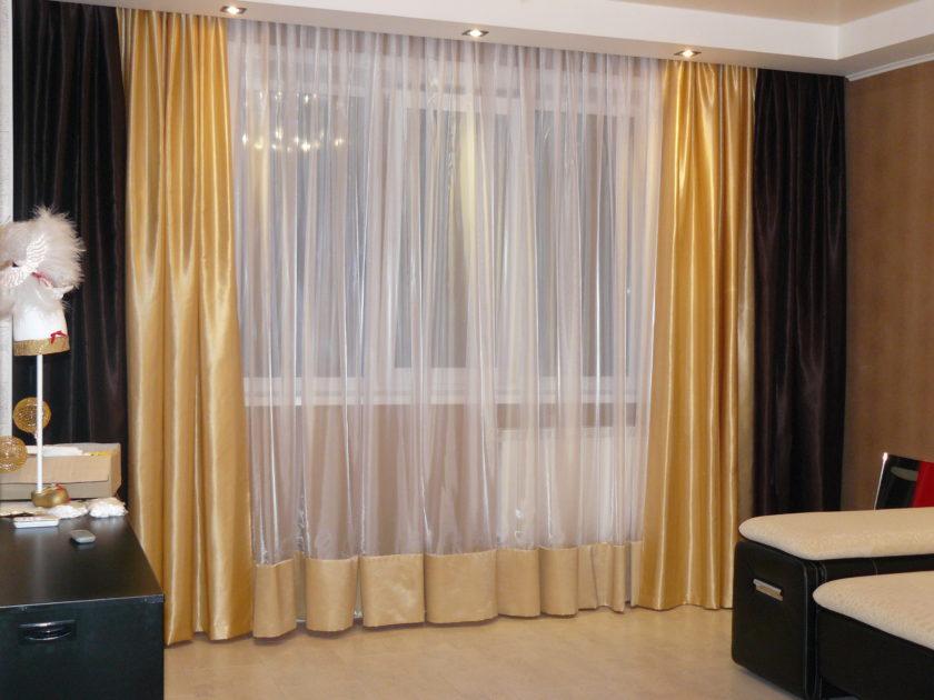 Золотистые портьеры на окне зала в хрущевке