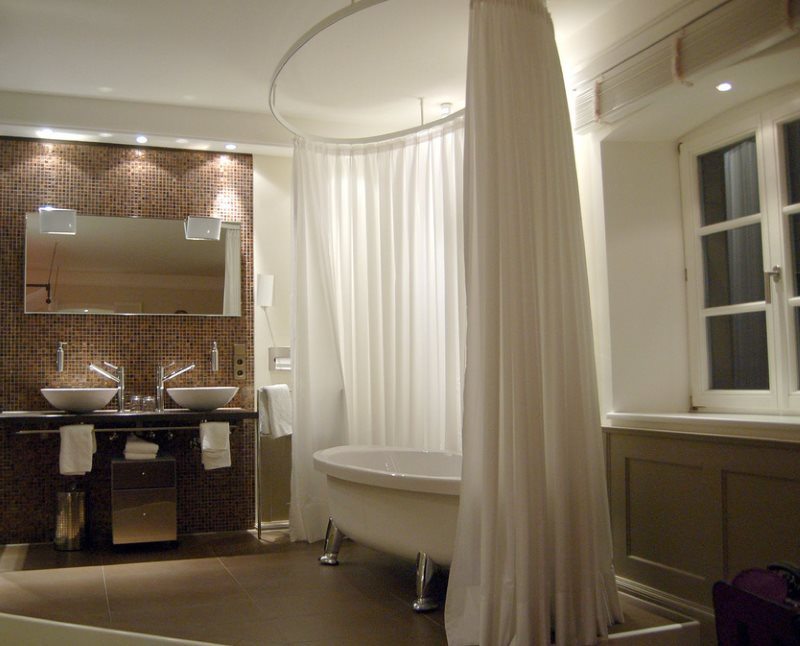 Длинная светлая занавеска вокруг овальной ванны