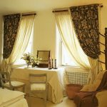 Двухслойные шторы для спальни со столом между двумя окнами