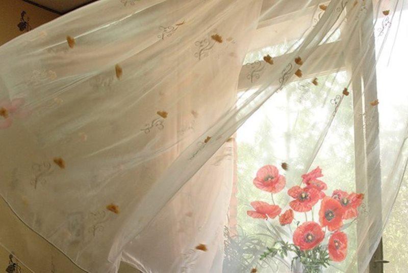 Легкая штора колышется от ветра из открытого окна