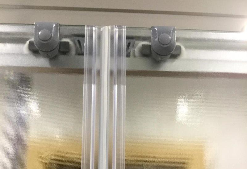 Ролики в верхней части раздвижной шторки из стекла