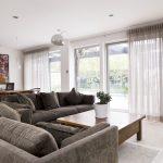 Серые диваны в гостиной с большими окнами