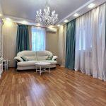 Бирюзовые шторы из атласа в гостиной городской квартиры