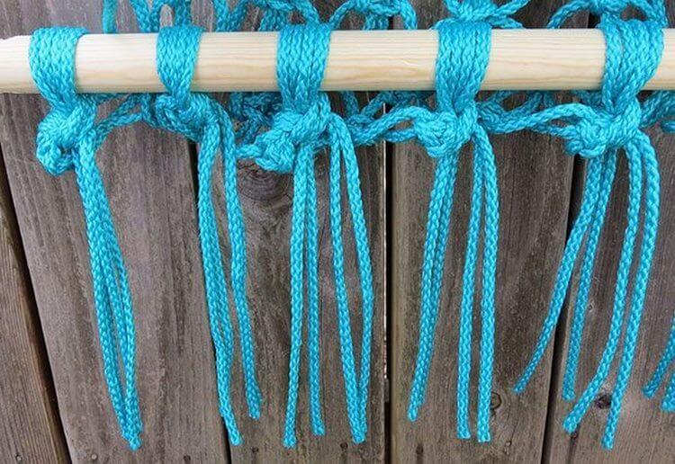 Плетение узлов из бирюзовой веревке на деревянной палке