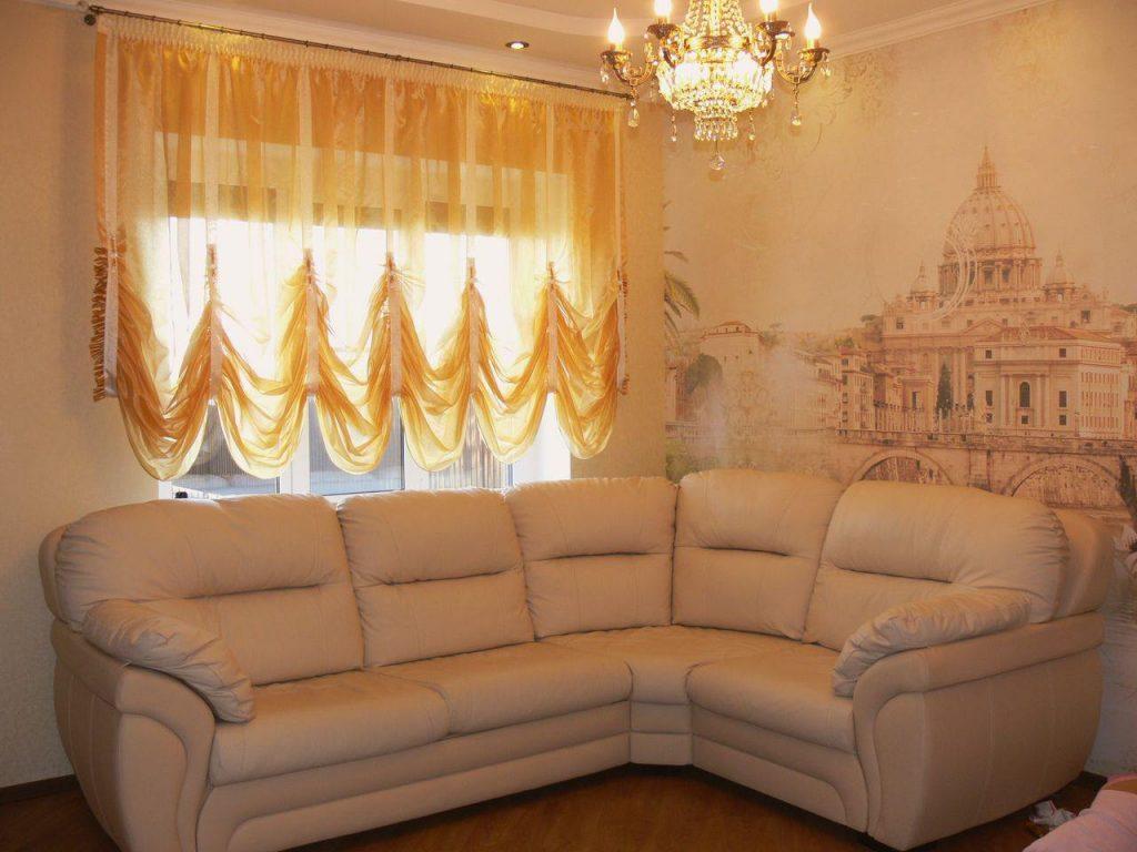 Угловой диван возле окна с короткими шторами желтого цвета