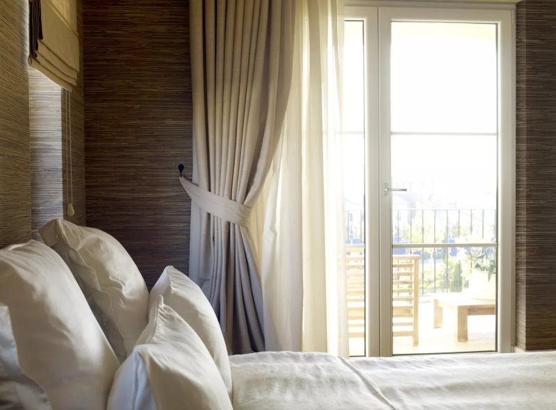 Бежевая штора из плотного материала на окне спальни