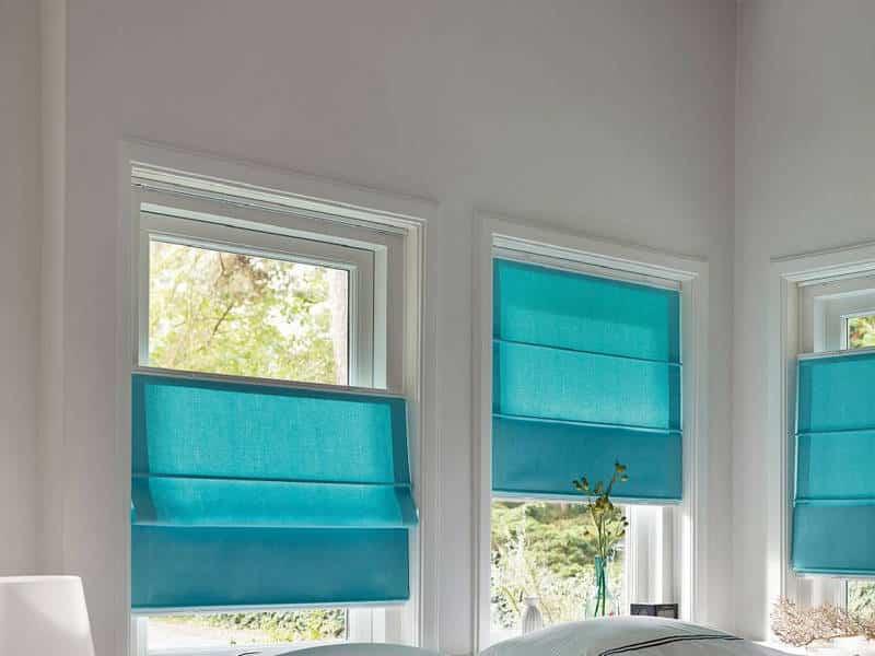 Голубые римские шторы на створках пластикового окна