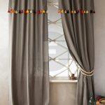 Серые шторы на кольцах с разноцветными кисточками