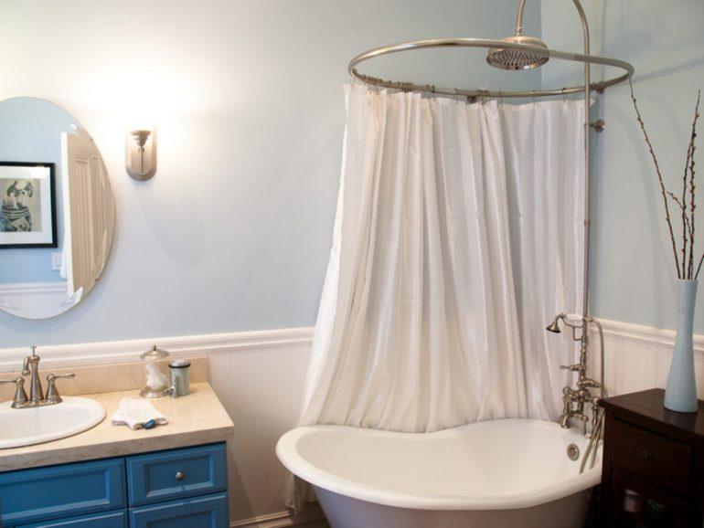 Мягкая шторка на овальном карнизе над небольшой ванной