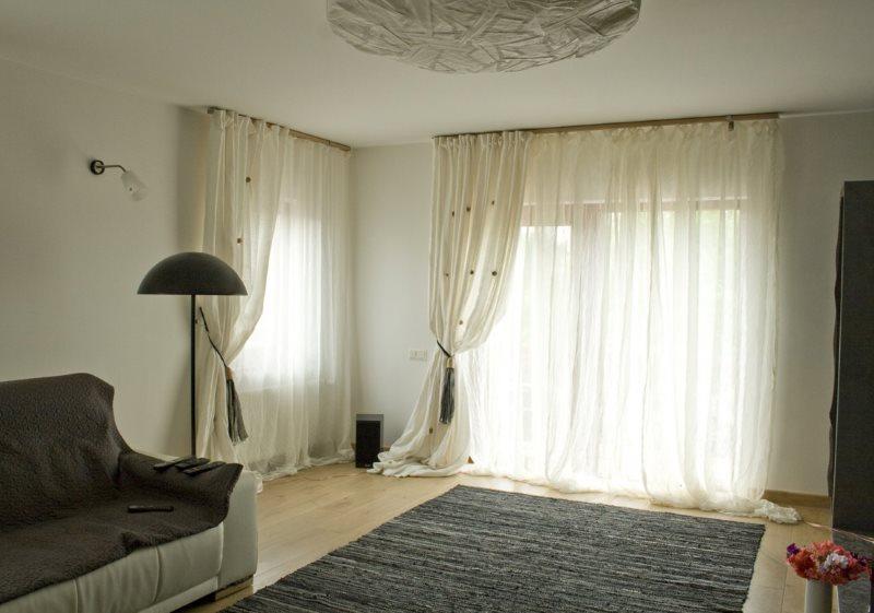 Оформлением окна гостиной длинными занавесками