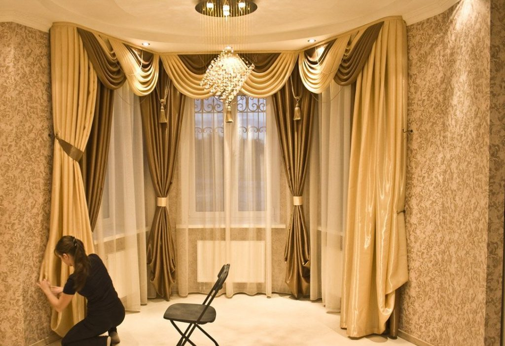 Красивые шторы с ламбрекеном на окнах эркера в зале частного дома
