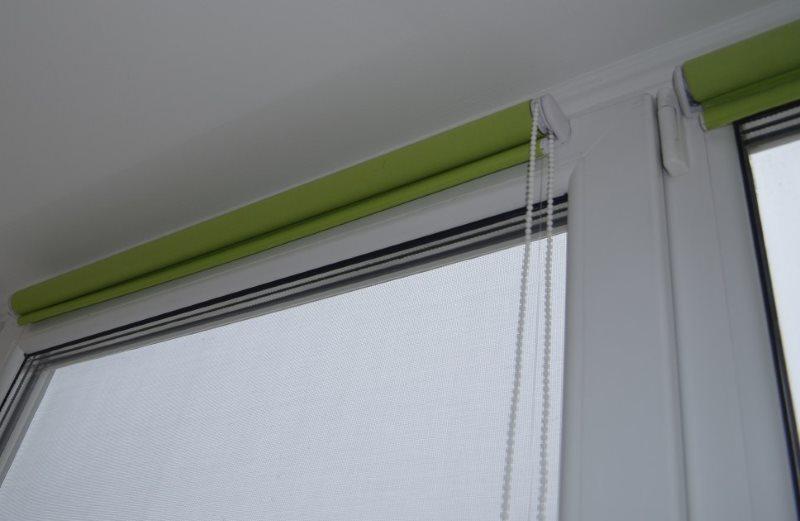 Свернутые рулонные шторы зеленого цвета на пластиковом окне