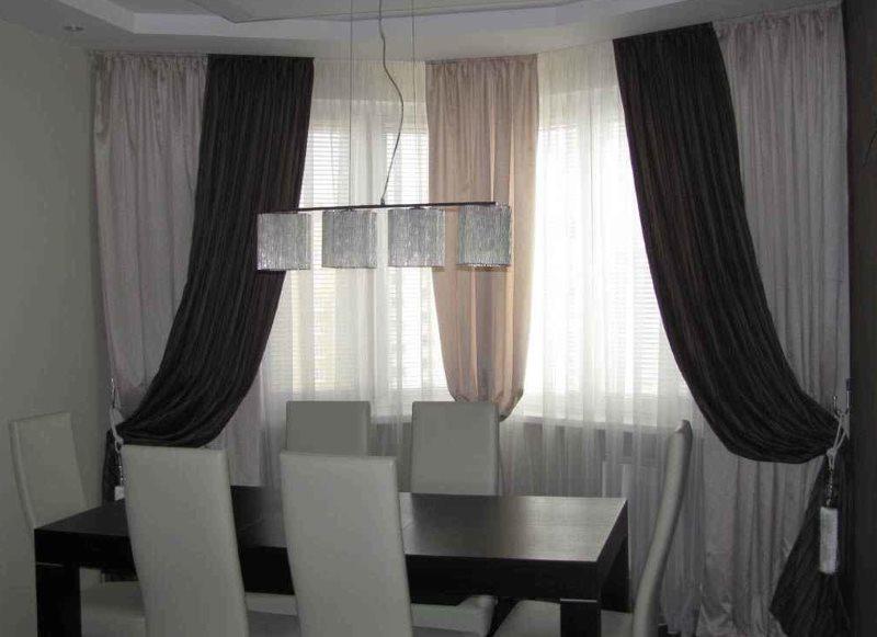 Декорирование окна гостиной плотными шторами из ткани разных цветов