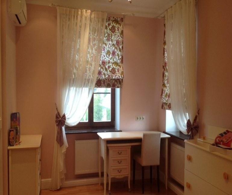 Письменный стол перед окнами с римскими шторами